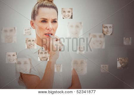 Serious businesswoman encircled by digital interface showing human faces