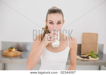 Serious young woman drinking glass of milk in the kitchen at home
