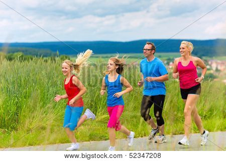 Family - mother, father and four children - doing jogging or outdoor sport for fitness on rural street