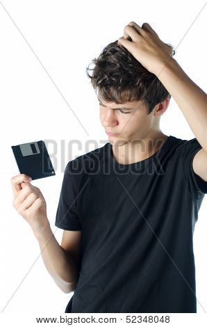Teenage Puzzled With Floppy Disk In His Hand