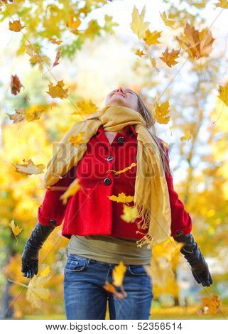 Happy Woman Throwing Autumn Leaves In The Park.