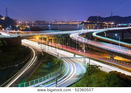 Night scene of cars light at highway and interchange in famous Guandu Bridge, Taipei, Taiwan, Asia.