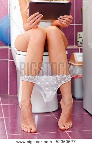 Woman with a mobile computer in the toilet