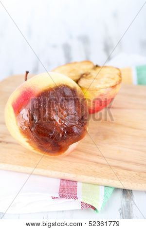Rotten apples on wooden board on table