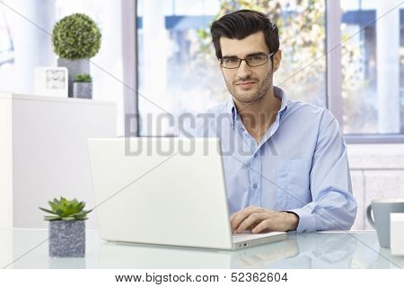 Handsome young businessman sitting at desk, working on laptop computer, looking at camera, smiling.