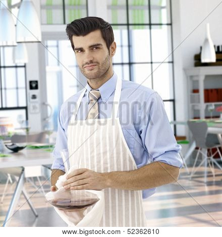 Waiter preparing red wine in trendy restaurant, looking at camera.