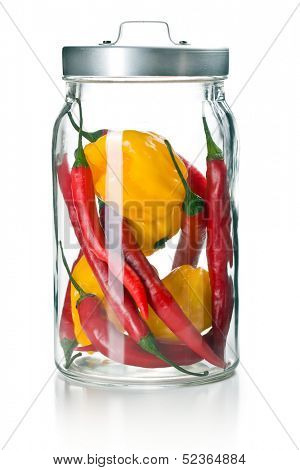 chili peppers and habanero in glass jar on white background