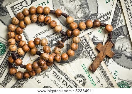 top view of rosary beads on us dollars background