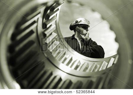 engineer, worker seen through a large gear axle shaft