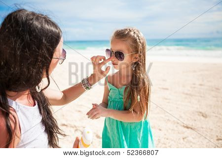 Mother Applying Sunblock Cream On Her Child Nose