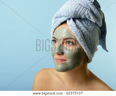 Beautiful young woman with clay facial mask, beauty treatment over blue