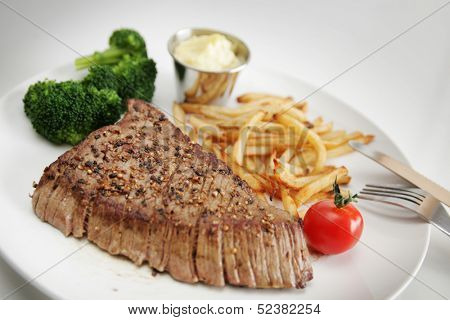 Beef steak served with vegetables and french fries