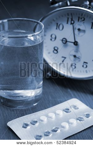 Birth control pills and a glass of water on a bedside table
