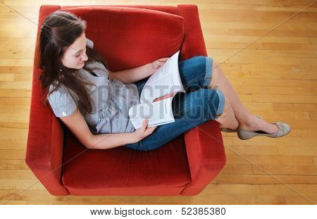 Teen sit in a sofa and read a magazine