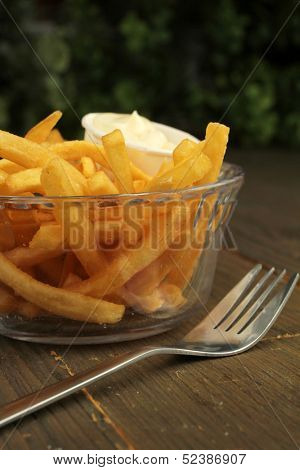 French fries with salt and mayonnaise in a clear bowl with fork
