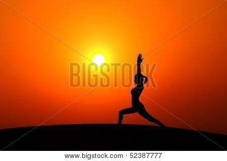 Silhouette of woman doing yoga meditation during sunset with natural golden sunlight on mountain.