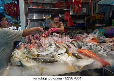 SINGAPORE - SEPTEMBER 19: A lady fishmonger sells fresh fish in a stall on September 19, 2013 in Toa Payoh Market, Singapore. The traditional Asian wet market still exist in this modern city.