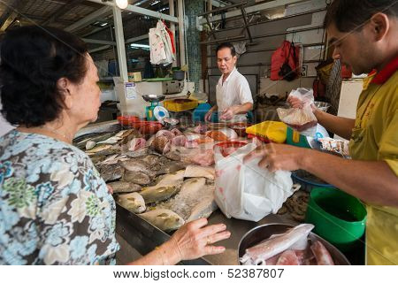 SINGAPORE - SEPTEMBER 19: A lady buys fresh fish from a stall on September 19, 2013 in Toa Payoh Market, Singapore. The traditional Asian wet market still exist in this modern city.