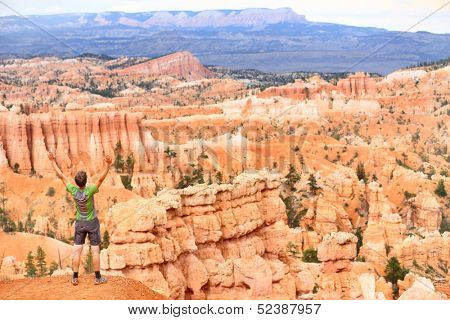 Cheering celebrating happy hiker in Bryce Canyon standing enjoying view with arms raised outstretched in winning success movement. Joyful hiking man tourist on travel in Utah, United States.