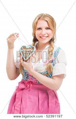 Bavarian woman in dirndl, holding lebkuchen.