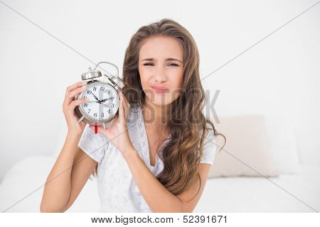Upset pretty brunette holding alarm clock in bright bedroom