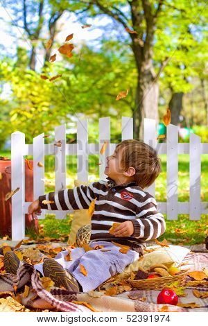 Little Boy Playing With  Leaves And Eating Cookies In The Autumn