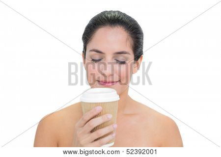 Smiling bare brunette smelling disposable cup on white background