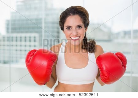 Sporty cheery brunette wearing boxing gloves in bright room