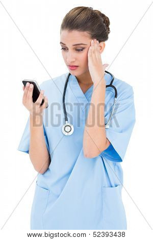 Puzzled brown haired nurse in blue scrubs using a mobile phone on white background