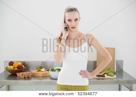 Pretty serious woman phoning in bright kitchen
