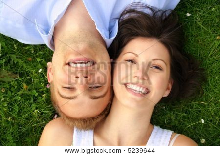 Smiling Couple Is Cuddle On A Green Meadow