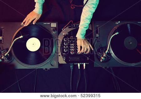 DJ manos en equipo cubierta y mezclador con disco de vinilo en fiesta