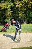 stock photo of ladies golf  - Female golf player put golf ball in sand - JPG