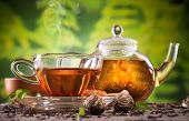 picture of black tea  - Cup of tea and teapot with blooming tea on blur green background - JPG