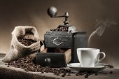 pic of coffee grounds  - hot cup of coffee with coffee grinder and coffee beans in jute bag on wooden table  - JPG
