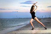 image of leggy  - Beautiful leggy brunette posing on the beach in black swimsuit - JPG