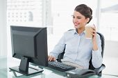 Smiling classy brown haired businesswoman holding a cup of coffee in bright office