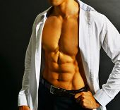 pic of nipples  - Muscular and tanned male torso isolated on black background - JPG