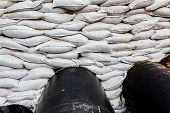 image of sandbag  - White sandbag bags are full with sand in wall formation to hold the Earth near traffic road - JPG