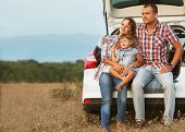stock photo of coat  - family in the mountains by car sitting in the trunk of PTFE coating - JPG
