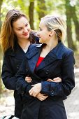 picture of fraternal twins  - Beautiful fraternal twin sisters glancing at each other while hugging and loving - JPG