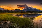 stock photo of ponds  - Golden early fall sunrise over the Canadian Rockies and Vermilion Lakes on the outskirts of Banff Canada - JPG
