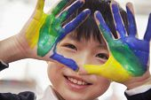 pic of finger-painting  - Portrait of smiling boy with fingers painted - JPG