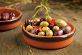 stock photo of kalamata olives  - Varitey of olives into into bowls on wooden table - JPG
