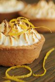 image of canapes  - Close up of a lemon tart with lemon zest on a wooden table - JPG