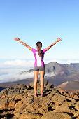 Success and achievement - hiking woman on top of the world. Happy cheering woman in winning gesture,