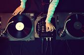 stock photo of mixer  - Dj hands on equipment deck and mixer with vinyl record at party - JPG