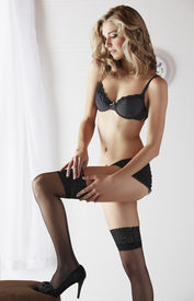 foto of panty-hose  - Sexy and beautiful young adult caucasian blonde woman in black lingerie and stockings in a light white bedroom - JPG