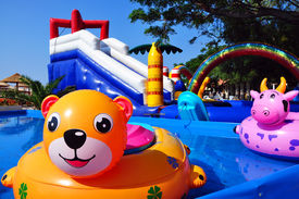 image of inflatable slide  - Inflatable toys in children sweeming pool and inflatable castle on background - JPG