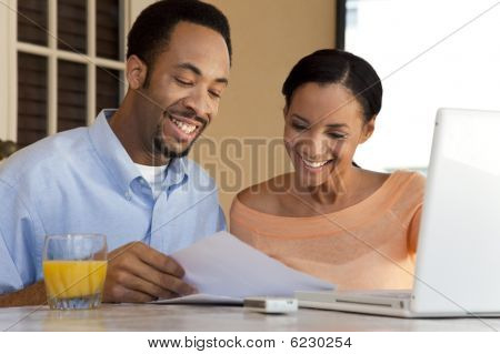 Happy African American Couple Working On Laptop Computer With Paperwork